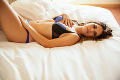Sexy girl lying on a bed Stock Photography