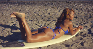 Sexy Girl Lying on Surfing Board at the Beach Royalty Free Stock Photos