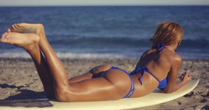 Sexy Girl Lying on Surfing Board at the Beach Stock Image