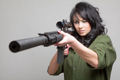 Sexy girl with machine gun. Beautiful girl wearing a green shirt and holding a machine gun aiming on grey background Stock Image