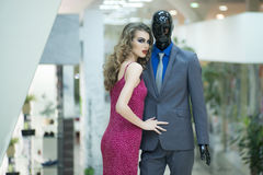 Girl and mannequin. Young girl with bright makeup and curly hair standing with male mannequin in formal clothes on shopping background, horizontal picture royalty free stock photo