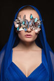 Sexy girl in Mask of butterflies. On her face.beauty fashion portrait of young woman in blue hood Royalty Free Stock Images