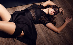 sexy girl with mask on face lying on the floor Royalty Free Stock Image