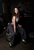 Sexy girl mechanic sitting on a tire holding a wrench in his hand. colorless life concept Royalty Free Stock Photo