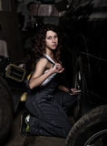 Sexy girl mechanic sitting on a tire holding a wrench in his hand. colorless life concept Stock Photography