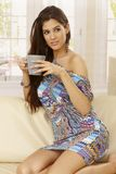 Sexy girl in mini dress drinking tea at home Stock Image