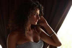 Girl next to window. Glamourous photo of attractive girl next to window stock photo