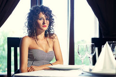 Sexy girl next to window. Glamourous photo of attractive girl sitting at table next to window Stock Photos