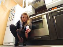 Sexy girl offering meat to her pet. Sexy blond girl in the kitchen in stockings and miniskirt offering meat to her pet. Pets perspective Royalty Free Stock Photos