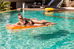Sexy girl with orange mattress at pool party Stock Photos