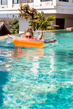 Sexy girl with orange mattress at pool party Stock Photo