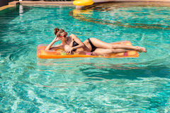 Sexy girl with orange mattress at pool party Royalty Free Stock Photo