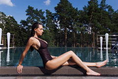 Sexy girl with perfect body and long legs sitting near the swimming pool in spa. Portrait of a sexy girl with perfect body and long legs sitting near the Royalty Free Stock Photography