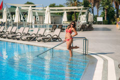 Sexy girl in a pink bathing suit sunbathing by the swimming pool. Sunny weather. Stock Photography