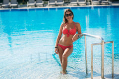 Sexy girl in a pink bathing suit sunbathing by the swimming pool. Sunny weather. Stock Photo