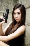 Sexy girl with pistol. Thai sexy girl holding the pistol Royalty Free Stock Image