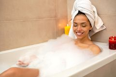 Sexy girl playing with foam in a bathtub royalty free stock photography