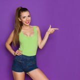 Sexy Girl Pointing. Beautiful young woman in lime green shirt and jeans shorts pointing. Three quarter length studio shot on violet background Royalty Free Stock Photos
