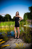 Sexy girl posing against pond and meadow Stock Photography