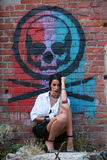 Sexy girl posing with beads in hand in a grunge building with grafittis on the wall Royalty Free Stock Photography