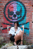 girl posing with beads in mouth in a grunge building with grafittis on the wall Royalty Free Stock Image