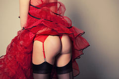 Sexy girl posing with her buttocks in red tanga, black stockings and red lace skirt Stock Photo