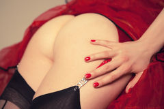Sexy girl posing with her buttocks in red tanga, black stockings and red lace skirt Royalty Free Stock Images