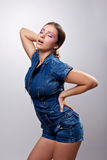 Sexy girl posing in jeans dress show desire. Sexy young girl posing in jeans costume show desire Royalty Free Stock Photo