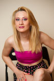 Sexy Girl Posing. Pretty sexy girl with blond hair posing in pink top and short skirt Royalty Free Stock Photos