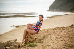 girl posing sitting on rocks at the beach royalty free stock image