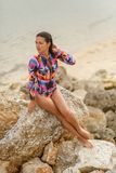 girl posing sitting on rocks at the beach stock photos