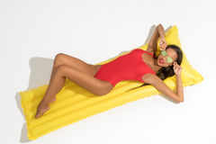 Girl posing on swimming mattress under sun isolated. Girl wearing sunglasses and red swimsuit lying on yellow swimming air mattress under sun isolated stock images