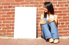 Girl With Poster. Fashionable girl with blank white poster against brick wall stock photography