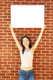 Girl With Poster. Fashionable girl with blank white poster against brick wall royalty free stock image