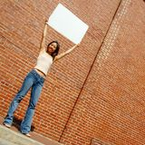 Girl With Poster. Fashionable girl with blank white poster against brick wall stock images