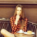 Girl licks finger. Girl pretty slim model in red checkered shirt and shorts licks finger on vintage coach in coffee cafe royalty free stock image
