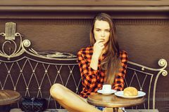 Girl licks finger. Girl pretty slim model in red checkered shirt and shorts licks finger on vintage coach in coffee cafe stock photos