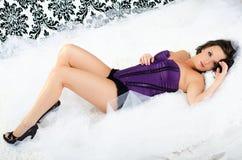 Sexy girl in purple lingerie corset boudoir fashion underwear. Studio portrait of sexy dark brown brunette girl / woman / female fashion boudoir glamour model Royalty Free Stock Photography