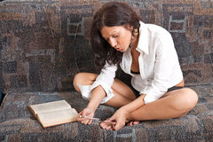 Sexy girl reads a book. And has manicure Royalty Free Stock Image