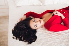 girl in red dress lying on bed with closed eyes.