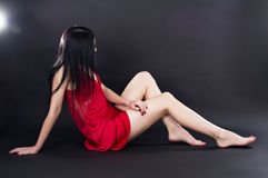 Sexy girl in a red dress seduces Royalty Free Stock Images
