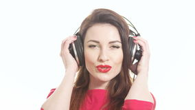 girl in red putting on big headphones and starts swinging to the music and dancing and kissing isolated on white background