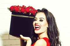 Sexy girl with red roses. Young pretty sexy woman or girl with cute smiling face and long brunette hair has fashionable makeup with red lipstick and dress holds stock photography