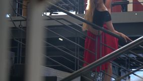 A girl in a red skirt and a black top is kneaded by holding onto the staircase railing in the mall, bit slow motion stock video
