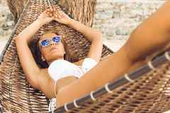 Sexy girl relax in hammock on tropic beach. Stock Photos