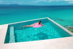 Girl relaxing on inflatable pink donut in the infinity swim. Ming pool at luxurious villa resort. Summer holiday idyllic top view. Beautiful destination. Travel royalty free stock photo