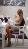Sexy girl in restaurant. Blonde sitting and posing in restaurant Stock Photos