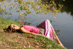 girl resting near pond Stock Image