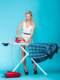 Sexy girl retro style ironing male shirt, woman housewife in domestic role. Royalty Free Stock Images