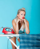 Sexy girl retro style ironing male shirt, woman housewife in domestic role. Traditional sharing household chores.  Pin up housework.  Vivid blue background Royalty Free Stock Photo